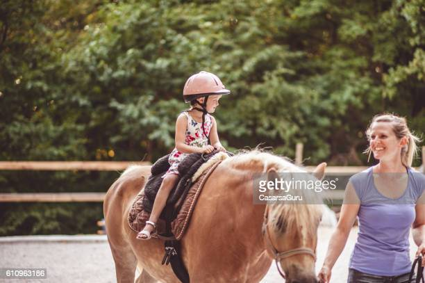 Little Girl Taking Horse-Riding Lessons