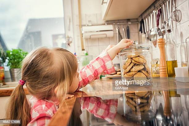Little Girl Taking Oatmeal Cookies from a Jar