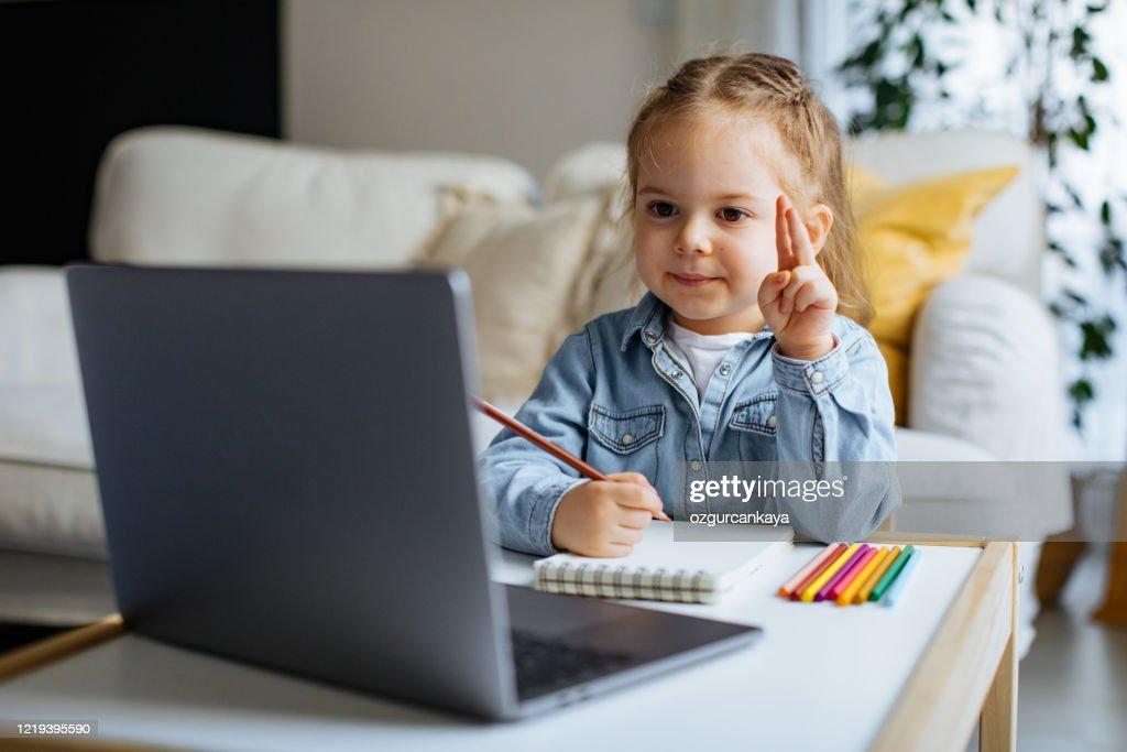 リビングルームでオンラインコースを取る小さな女の子 : ストックフォト