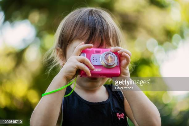 little girl taking pictures with toy camera outdoors - camera girls - fotografias e filmes do acervo