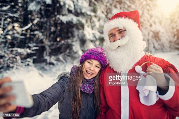 Little girl taking selfie with the Santa Claus