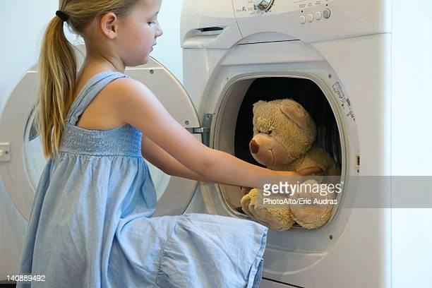 Little girl taking teddy bear out of dryer