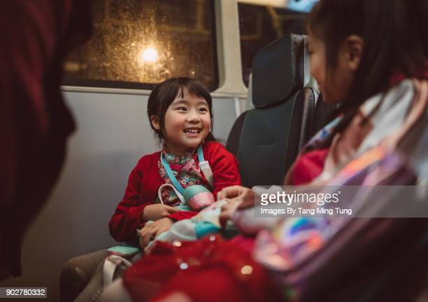 Little girl talking to her sibling joyfully while travelling in a bus at night.