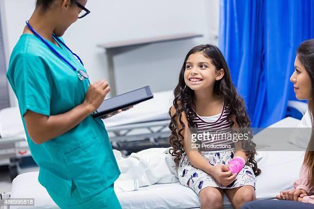 Kleines Mädchen im Gespräch mit Krankenschwester im Notfall-Zimmer