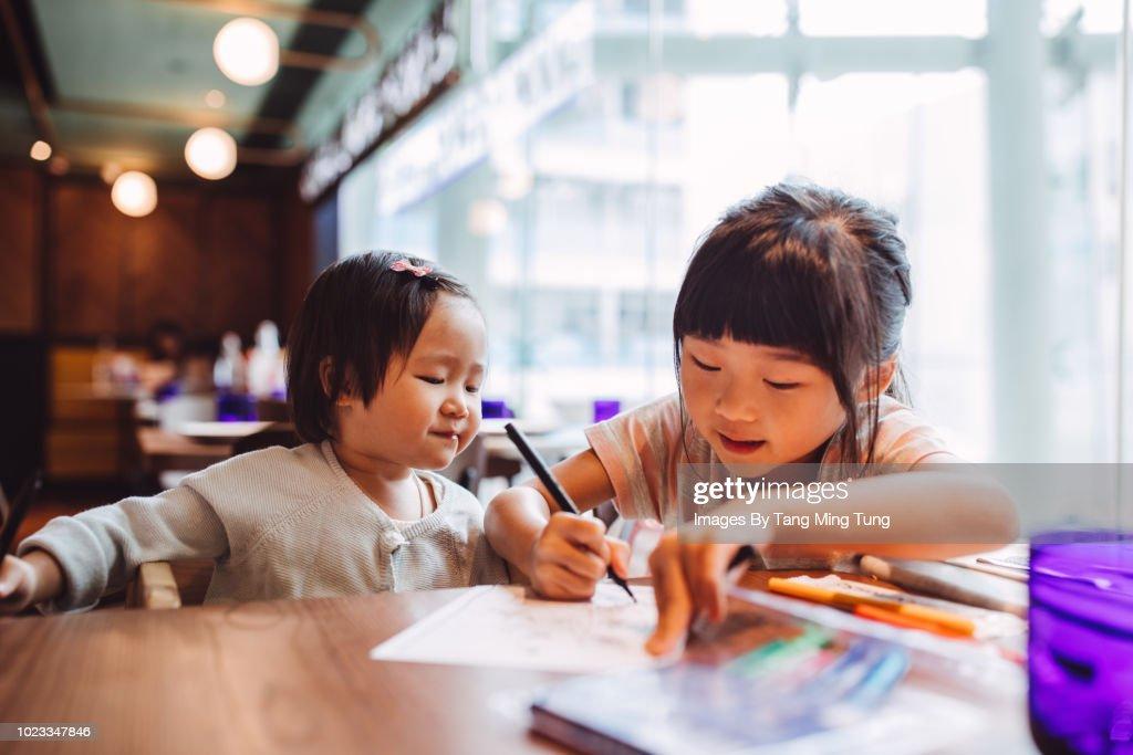 Little girl teaching her little toddler sister to draw joyfully in a restaurant. : Stock Photo