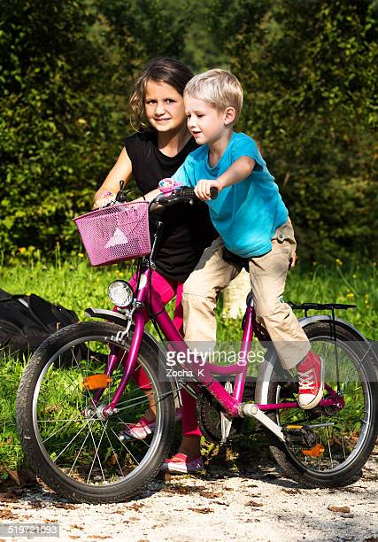 Little girl teaching her younger brother to ride bike