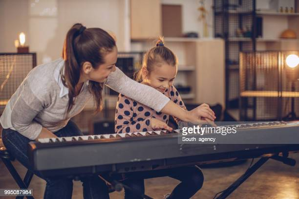 little girl teaching to play synthesizer - keyboard player stock photos and pictures