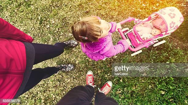 kleines mädchen veralbern ihre eltern im park - frau beine breit stock-fotos und bilder
