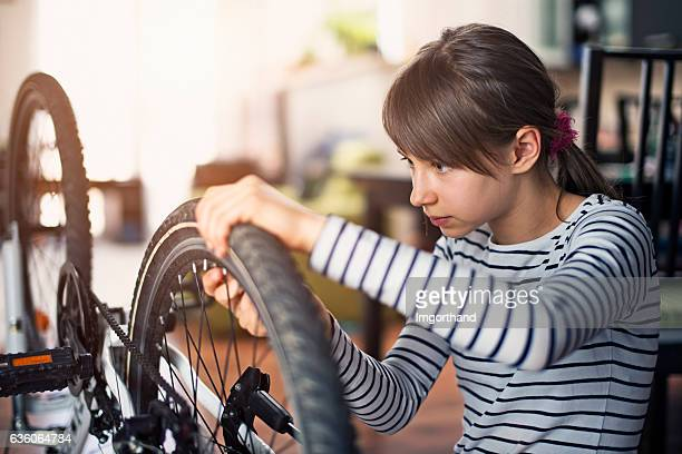Little girl tending to her bicycle at home