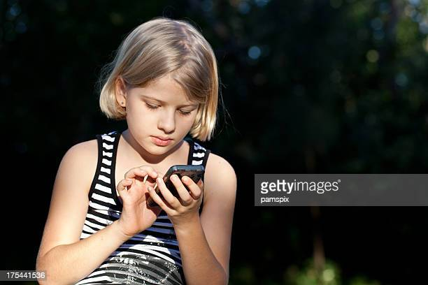 Little girl texting on mobile phone outdoors park
