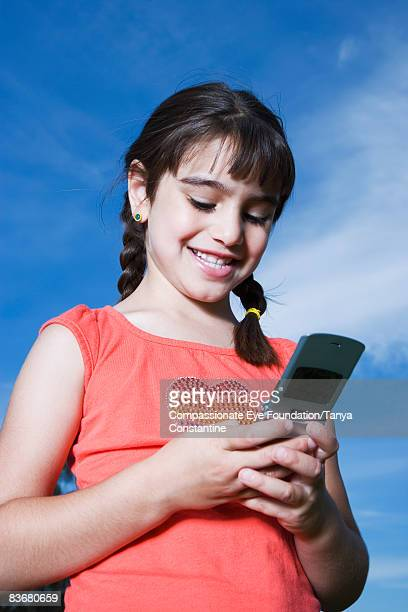 "little girl texting on mobile phone - ""compassionate eye"" stock pictures, royalty-free photos & images"