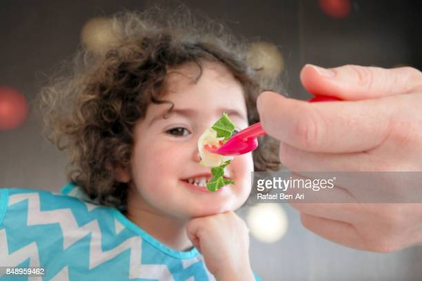 Little girl thinking about eating healthy food