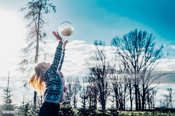 Little girl throwing a snow-filled crystal ball