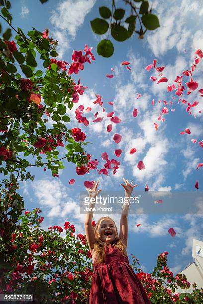 Little girl throwing red rose petals, smiling