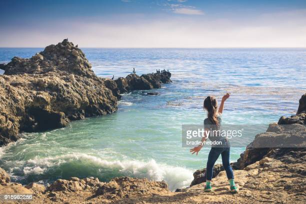 Little girl throwing rocks into the ocean