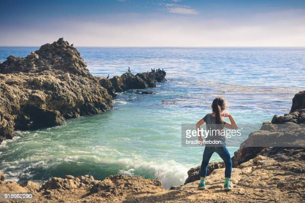 Little girl throwing rocks into the ocean