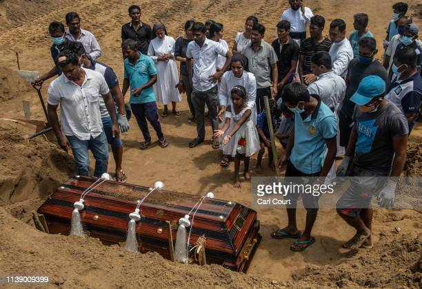 A little girl throws earth on a coffin during the funeral of a person killed in the Easter Sunday attack on St Sebastian's Church on April 24 2019 in...