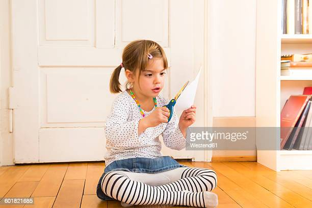 little girl tinkering with paper and scissors - children pantyhose stock photos and pictures