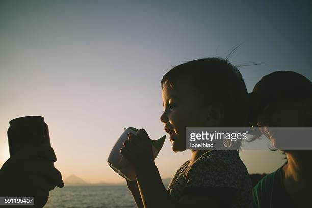 Little girl toasting her cup at sunset