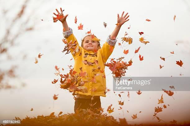 Kleines Mädchen Herumwerfen Blätter in die Luft