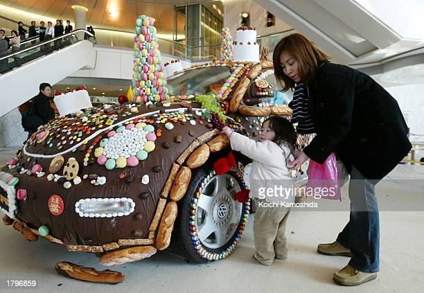 A little girl touches a chocolatecoated Volkswagen February 14 2003 in Tokyo In Japan women give chocolate to men on Valentine's Day to show their...