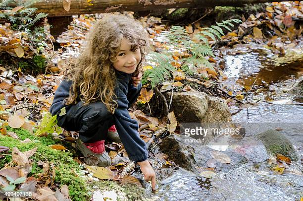 Little girl touching cold water of small river