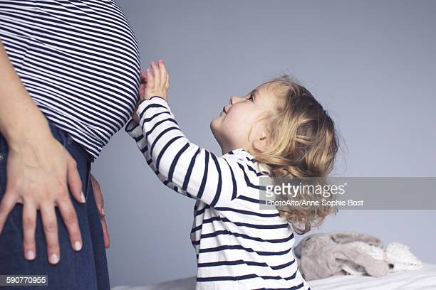 Little girl touching mothers pregnant stomach, cropped