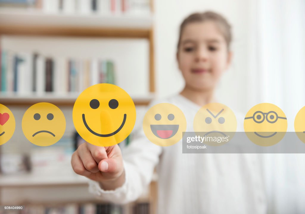 Little girl touching the smiley emoji icon on the touch screen : Stock Photo