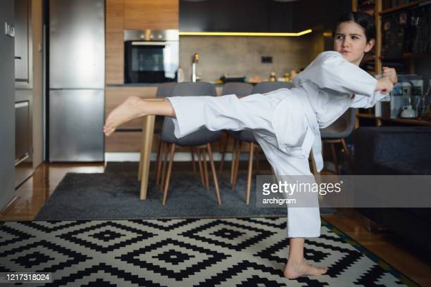 little girl trains taekwondo at home - martial arts stock pictures, royalty-free photos & images