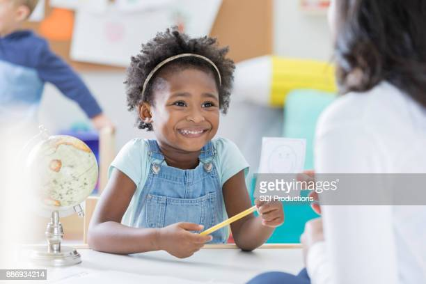 Little girl tries hard to remember flash card answer