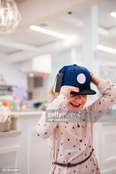 Liten flicka försöker en hatt i barn lagra.