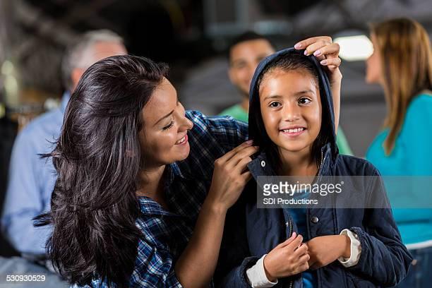 Kleines Mädchen versucht auf Jacke im winter Kleidung Spende drive