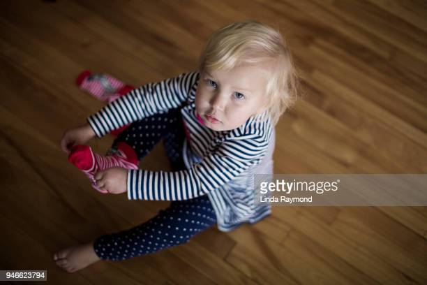 bambina cercando di mettere i calzini - sforzo foto e immagini stock