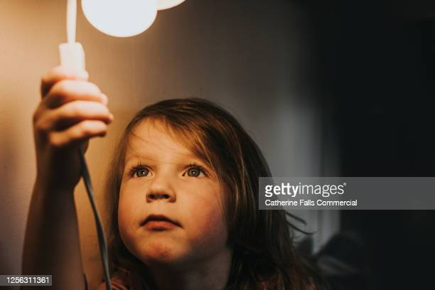 little girl turning on a light - turning on or off stock pictures, royalty-free photos & images