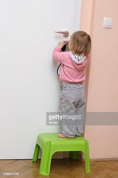 Little girl unlocking the door