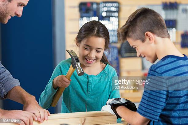 Little girl uses hammer in daycamp at local makerspace
