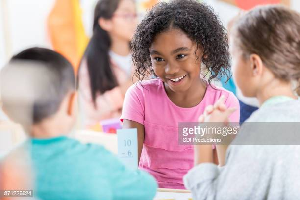 little girl uses mathematics flash card to quiz friend - peer to peer stock pictures, royalty-free photos & images