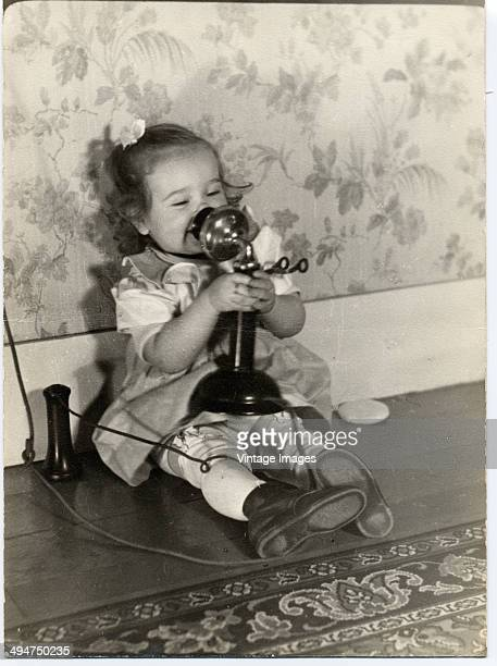 A little girl using a candlestick telephone circa 1940