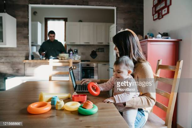 a little girl using a laptop with her mom while the dad is cooking in the kitchen - pandemic illness stock pictures, royalty-free photos & images