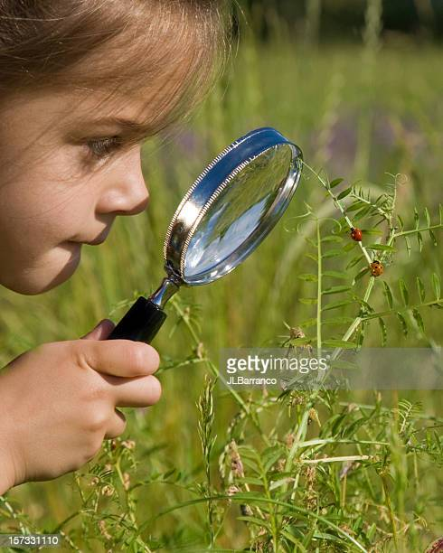 A little girl using a magnifying glass outside