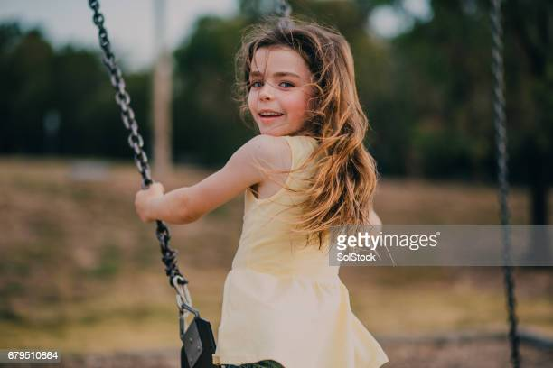 Little Girl Using a Swing in a Park