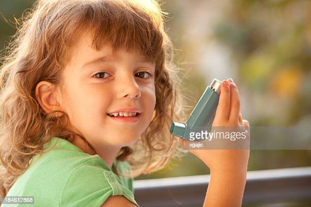 little girl using asthma inhaler outdoor - asthmatic stock photos and pictures