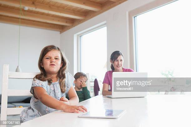 Little girl using digital tablet, mother and brother using laptop in background