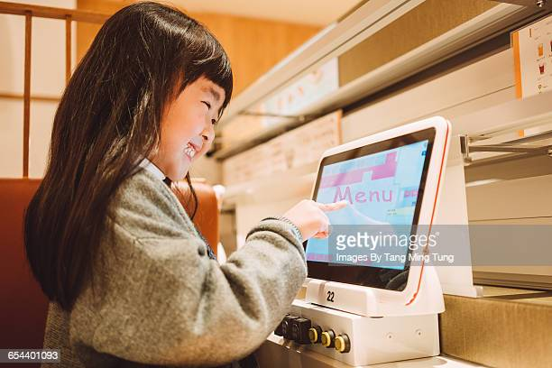Little girl using electronic menu in restaurant