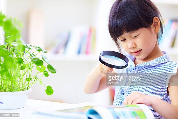 little girl using magnifying glass reading book