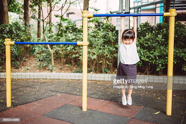 Little girl using parallel bars in playground