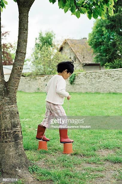Little girl using plastic buckets as stilts, side view