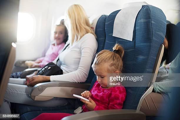 Kleines Mädchen mit Smartphone im Flugzeug.