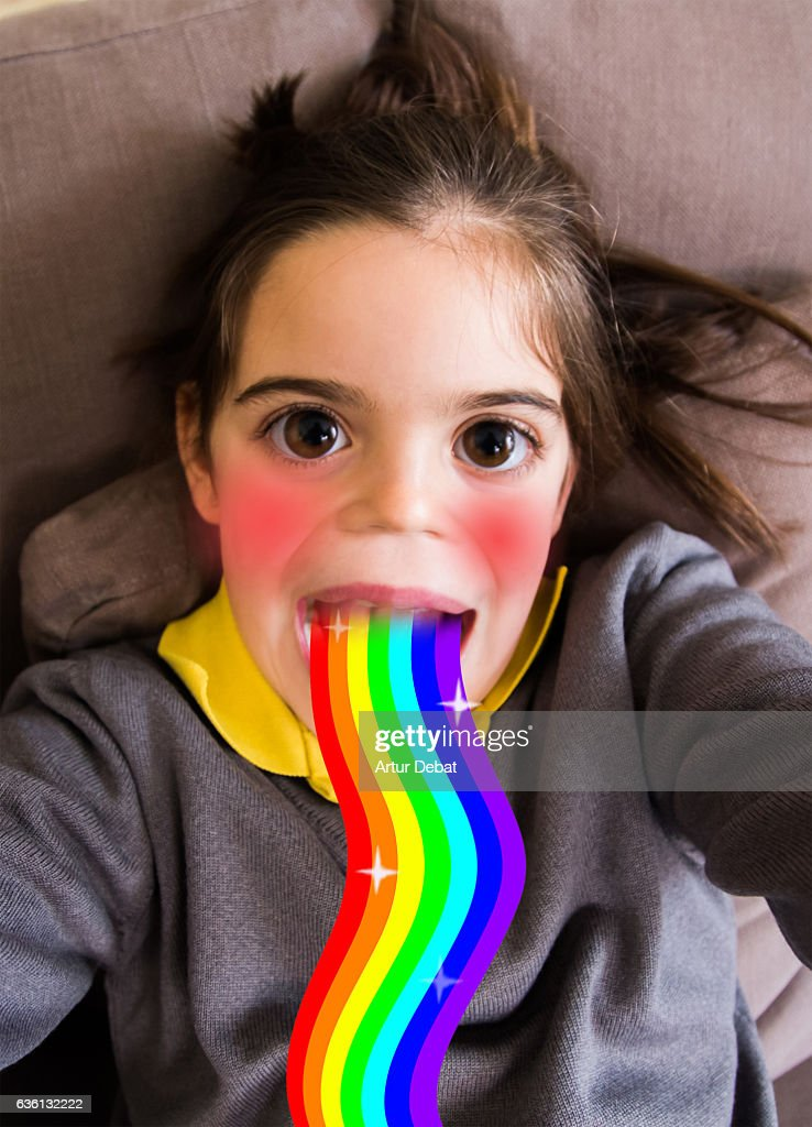 Little girl using smartphone application changing her face. : Stock Photo