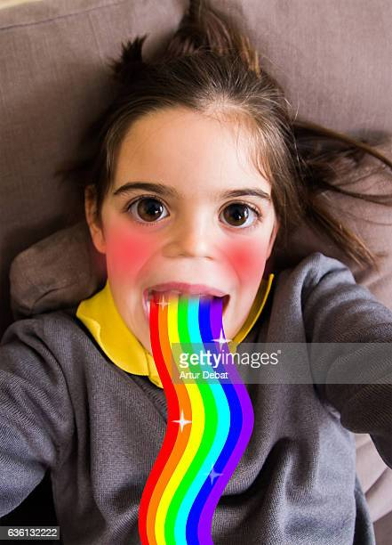 little girl using smartphone application changing her face. - cartoon ストックフォトと画像